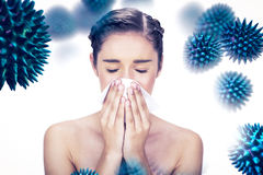 Composite image of sick young model blowing her nose. Sick young model blowing her nose  against virus Royalty Free Stock Photo