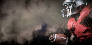 Composite image of side view of aggressive sportsman playing american football