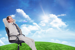 Composite image of side view of businessman leaning back in his chair Stock Photo