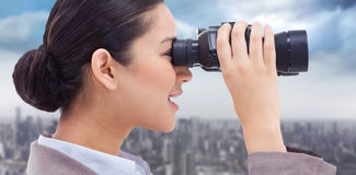 Composite image of side view of a businesswoman looking through binoculars Stock Image