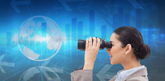 Composite image of side view of a businesswoman looking through binoculars Royalty Free Stock Image