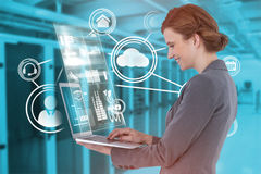 Composite image of side view of businesswoman using laptop computer. Side view of businesswoman using laptop computer against view of data technology Stock Photography