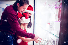 Composite image of side view of family in christmas attire looking at display of wrist watch. Side view of family in Christmas attire looking at display of wrist Stock Photo