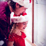 Composite image of side view of father and daughter in christmas attire looking at jewelry display Royalty Free Stock Photography