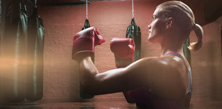 Composite image of side view of female boxer with fighting stance. Side view of female boxer with fighting stance against punching bags in red boxing area royalty free stock photography