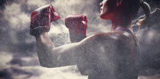 Composite image of side view of female boxer with fighting stance. Side view of female boxer with fighting stance against splashing of yellow color powder stock photos