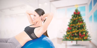 Composite image of side view of a fit woman stretching on fitness ball. Side view of a fit woman stretching on fitness ball against home with christmas tree Royalty Free Stock Photography