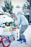 Composite image of side view of girl putting presents on sled Royalty Free Stock Photo