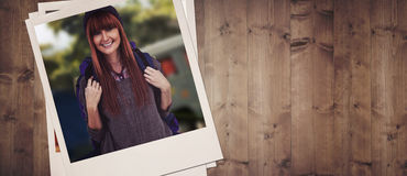 Composite image of side view of a hipster woman with a travel bag. Side view of a hipster woman with a travel bag against wooden planks Royalty Free Stock Photography