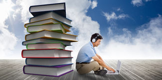 Composite image of side view of man listening music while using laptop Stock Image