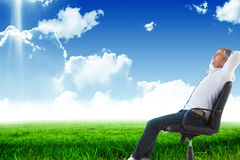 Composite image of side view of man sleeping on chair. Side view of man sleeping on chair against blue sky over green field Royalty Free Stock Photography