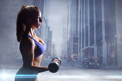 Composite image of side view of sexy woman lifting dumbbell Stock Photo