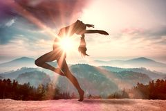 A Composite image of side view of a sporty young woman stretching Royalty Free Stock Images