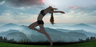 A Composite image of side view of a sporty young woman stretching Royalty Free Stock Image