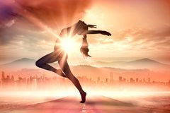A Composite image of side view of a sporty young woman stretching. Side view of a sporty young woman stretching against sun shining over road and city Royalty Free Stock Photography