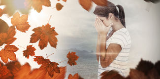 Composite image of side view of upset woman covering face Stock Image