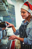 Composite image of side view of waitress wearing santa hat using espresso maker Royalty Free Stock Photos