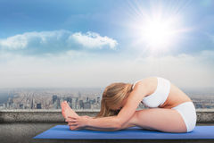 Composite image of side view of woman doing the paschimottanasana pose Royalty Free Stock Images