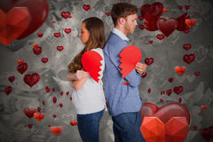 Composite image of side view of young couple holding broken heart 3D. Side view of young couple holding broken heart against love heart pattern 3D Stock Images