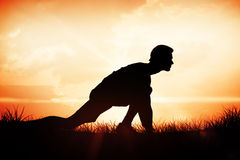 Composite image of side view of a young man in ready to run posture Royalty Free Stock Images
