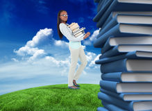 Composite image of side view of young woman carrying a pile of books Stock Photos