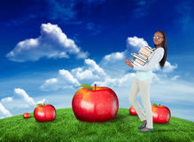 Composite image of side view of young woman carrying a pile of books Royalty Free Stock Images