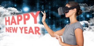 Composite image of side view of young woman gesturing while using virtual video glasses. Side view of young woman gesturing while using virtual video glasses Royalty Free Stock Photo