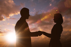 Composite image of silhouette of business people shaking hands Stock Photo