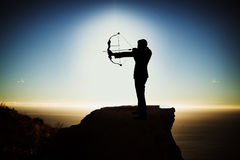 Composite image of silhouette businessman taking aim with bow and arrow Stock Image