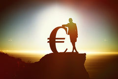 Composite image of silhouette beside euro symbol Stock Images