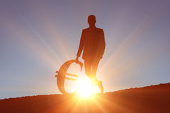 Composite image of silhouette beside euro symbol Royalty Free Stock Photo