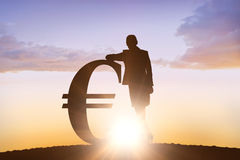 Composite image of silhouette beside euro symbol Stock Image