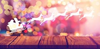 Composite image of silhouette of santa claus and reindeer. Silhouette of santa claus and reindeer against composite image of wooden shelf against christmas tree Royalty Free Stock Photos