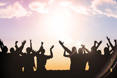 Composite image of silhouetters celebrating Royalty Free Stock Photos