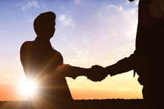 Composite image of silhouettes shaking hands Royalty Free Stock Image