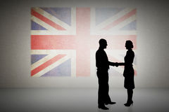Composite image of silhouettes shaking hands. Silhouettes shaking hands against union jack flag in grunge effect Royalty Free Stock Photo