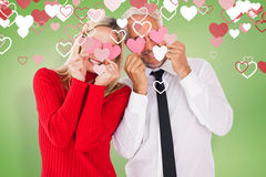 Composite image of silly couple holding hearts over their eyes Royalty Free Stock Photo