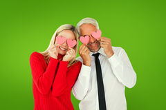 Composite image of silly couple holding hearts over their eyes Royalty Free Stock Image
