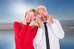 Composite image of silly couple holding hearts over their eyes Royalty Free Stock Images