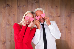 Composite image of silly couple holding hearts over their eyes Stock Image