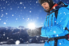 Composite image of skier with backpack wearing gloves. Skier with backpack wearing gloves against snow covered mountains against clear sky Royalty Free Stock Photography