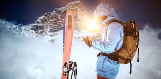 Composite image of skier with skis and backpack using mobile phone. Skier with skis and backpack using mobile phone against view of snowy mountain range and Royalty Free Stock Photos