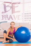 A Composite image of slim blonde sitting beside exercise ball smiling at camera Stock Image