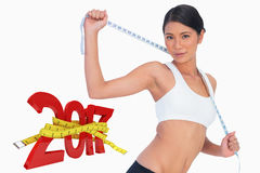 Composite image of slim woman holding her measuring tape Royalty Free Stock Image
