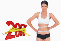 Composite image of slim woman measuring her waist stock photography