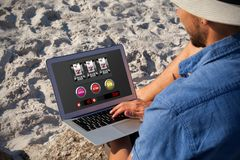 Composite image of slot machine with icons on mobile screen. Slot machine with icons on mobile screen against man using laptop on the beach Royalty Free Stock Photography