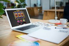 Composite image of slot machine on mobile screen. Slot machine on mobile screen against laptop and color swatch on table stock photography