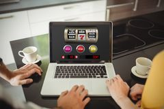 Composite image of slot machine with text and numbers on mobile screen. Slot machine with text and numbers on mobile screen against couple using laptop in Royalty Free Stock Image