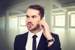 Composite image of smart businessman speaking on the phone Royalty Free Stock Images