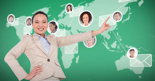 Composite image of smiling asian businesswoman pointing Royalty Free Stock Images